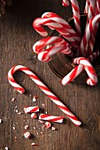 Christmas candy canes in a gold traditional mug and one cane on a rustic wooden surface