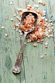 Vinatge silver spoon full of Himalayan pink sea salt on an aqua blue green wooden rustic surface