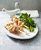Lactose-free turkey skewers with pineapple and red pepper, served with lamb's lettuce