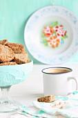 Schale mit glutenfreien Plätzchen aus Buchweizenmehl und Kokosblütenzucker, daneben Kaffee im Emaillebecher