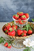 Fresh strawberries in a glass bowl on a white plate with a white paper flower