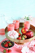 Strawberry and nectarine smoothies on a golden stand