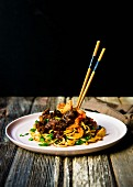 Pan-fried udon noodles with slow braised beef shank, kimchi and spring onions