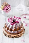 Napfkuchen mit Puderzucker und Blumendeko