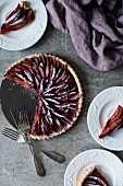 Plum tart dusted in icing sugar with slices cut out