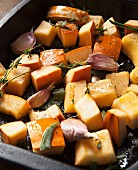 Raw pumpkin pieces with garlic, sage and thyme in a roasting tray