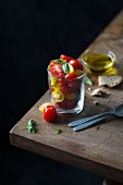 Fresh cherry tomato salad with basil and olive oil served in a glass