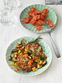 Vegan herb potato cakes with rosemary vegetables and tomato salad