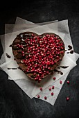 Heart-shaped chocolate cake with chocolate glaze and pomegranate seeds