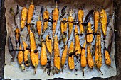 Oven cooked carrots with herbs and sauce on a baking sheet (top view)