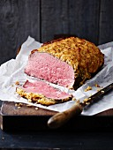 A joint of roast beef with an onion crust and one slice cut off