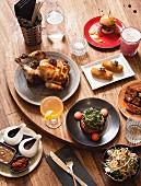 Hähnchen mit Misobutter, Kroketten, Slider, Sticky Pork, gegrillte Wassermelone, Salat und Cocktails im Restaurant (Melbourne, Australien)
