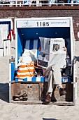 Person mit Zeitung am Strand von Westerland, Sylt, Deutschland