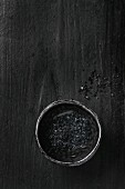 Bowl of black salt over black background