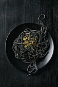 Cooked black pasta with saffron salt over black background