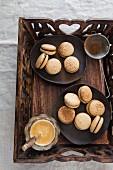 Macarons und Kaffee auf Holztablett
