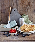 Pancakes with berries and cooking utensils