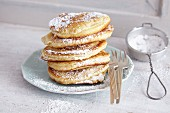 A stack of American buttermilk pancakes decorated with icing sugar
