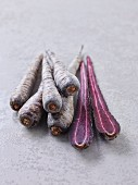 Whole and halved purple carrots