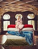 Blonde Frau in rosa Paillettenkleid und Pumps sitzt auf mehreren Matratzen