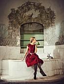 Blonde Frau in rotem Satin-Cocktailkleid, Strassschmuck und schwarzen Pumps küsst Frosch