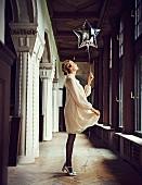 Blonde Frau in cremefarbenem Chiffonkleid, gepunkteter Strumpfhose und silbernen T-Steg-Pumps