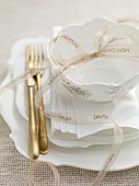 A Christmas table setting with a ribbon and gold cutlery