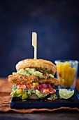 A burger with chicken breast, pineapple, avocado, prawns and mango chutney