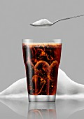 Glass of cola in front of pile of sugar