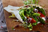 A wrap with vegetables and salad
