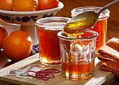 Homemade marmalade being put into jars with whole oranges in the background