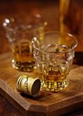 Two glasses of Scotch whisky on a wooden board