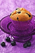 A blueberry muffin on a small purple glass cake stand sitting on a purple crushed paper background