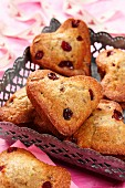 Heart shaped muffins in a metal basket on a pink background with pink ribbon with heart pattern