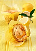 Lemon and sultana muffins on a yellow background with fresh lemons and leaves