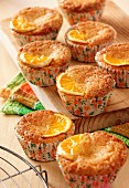 Deveral orange and semolina muffins on a wooden board sitting on a wooden table top.