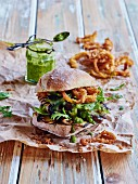 Burger with aubergines, crispy onion rings and chimichurri