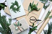 Weihnachtsgeschenke mit Zweigen und Blättern dekorieren