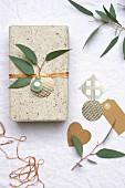 Geschenk mit Weihnachtskugel und Blätterzweig dekoriert