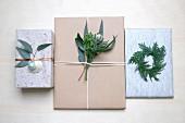 Weihnachtsgeschenke mit Zweigen, Blättern und Weihnachtskugel dekoriert
