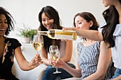 Woman pouring bottle of white wine for friends