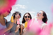 Laughing women eating flavored ice outdoors