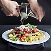 Hands grating parmesan cheese on penne pasta