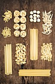 Different types of Italian uncooked pasta on rustic wooden table background