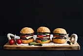 Fresh homemade burgers on wooden serving board over black background