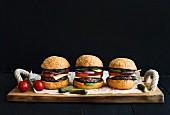 Selbst gemachte Burger auf Holzbrett vor schwarzem Hintergrund