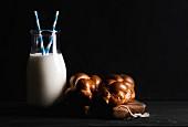 Eine Flasche Milch und Milchbrötchen auf rustikalem Holzbrett vor schwarzer Hintergrund