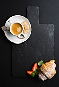 Espresso coffee cup and croissant with fresh strawbwrries on black slate stone board