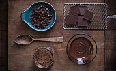 Chocolate baking supplies laid out on a rustic wood surface with antique props