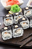 Sushi rolls with eel and creamcheese on a wooden board